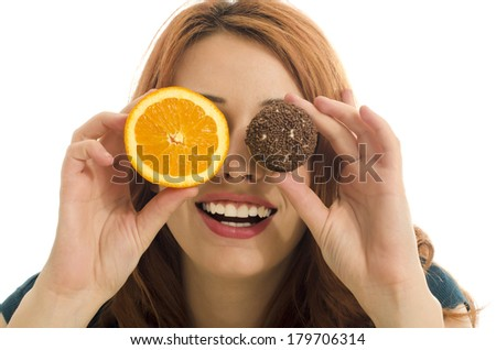 Woman holding in front of her eyes one orange and one candy,choosing between healthy and unhealthy food