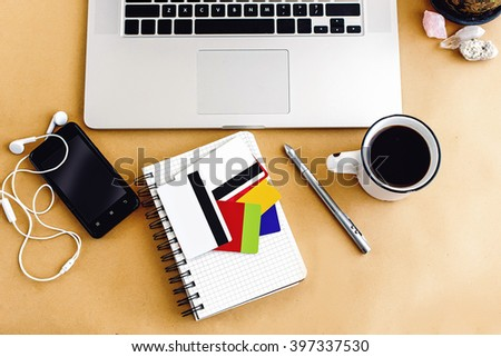 woman holding in hand different credit and bonus cards on background of laptop notebook on craft table, shopping and paying bills online - stock photo