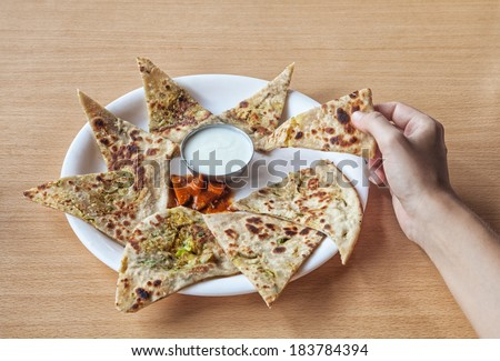 Woman holding Indian traditional aloo paratha in restaurant     - stock photo