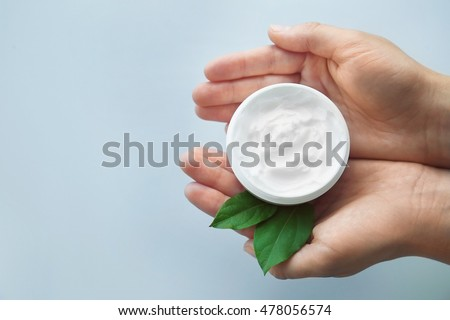Woman holding jar with cream and green leaves on white background