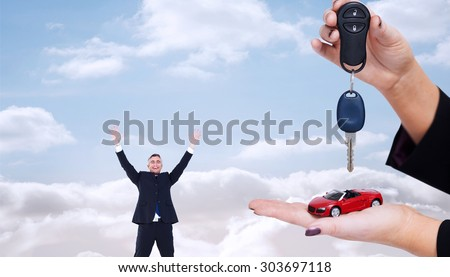 Woman holding key and small car against cloudy sky - stock photo