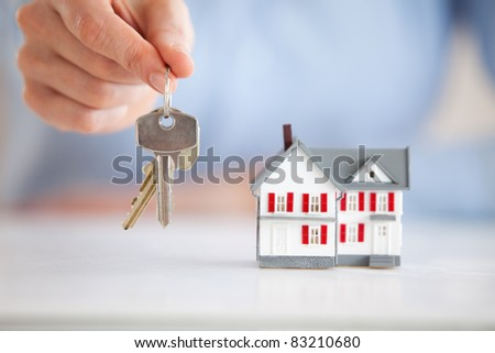 Woman holding keys next to a model house in an office - stock photo