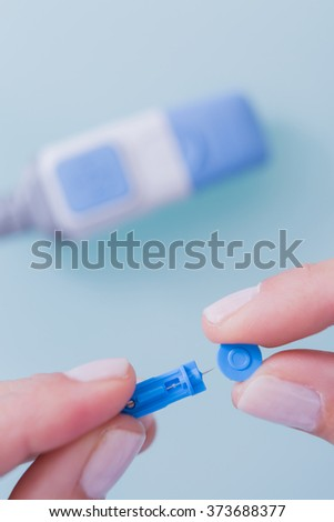 Woman holding lancing needle. Diabetes theme. Unfocused glucometer. Close-up, from above. Unrecognizable