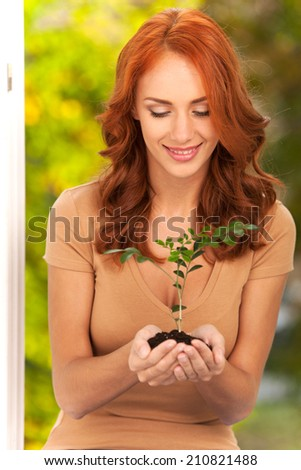 Woman holding little plant in her hands. Woman's hands holding soil with plant and smiling - stock photo