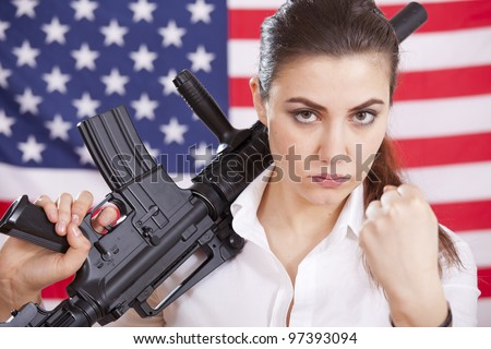 woman holding machine gun and threatening with clenched fist over american flag - stock photo
