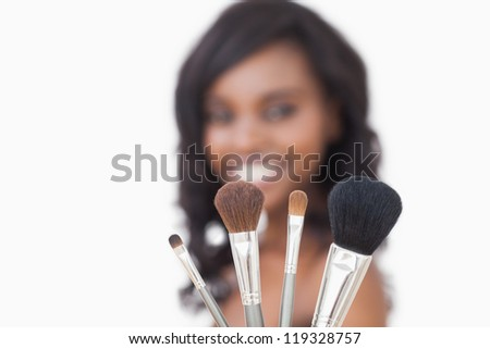 Woman holding makeup brushes while smiling