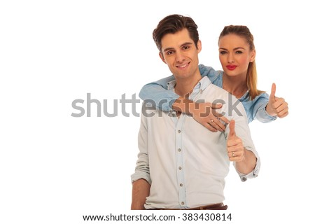 woman holding man from behind while both show thumbs up sign looking at the camera in isolated studio background - stock photo