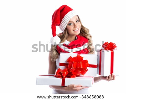 Woman holding many Christmas gifts in her arms wearing santa hat. - stock photo