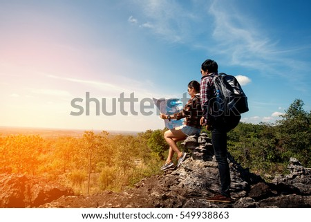 Woman holding map and man looking map,Happy tourists sightseeing mountain with map
