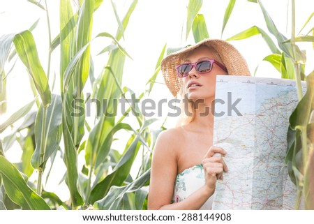 Woman holding map while standing amidst plants outdoors - stock photo
