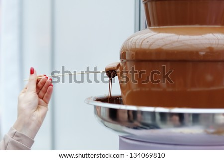 Woman holding marshmallow and frosting its in chocolate fondue fountain - stock photo