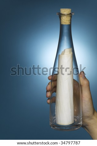 Woman holding message in bottle, close-up of hand - stock photo