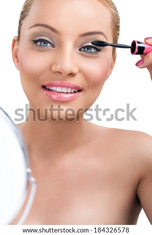 Woman holding mirror and applying mascara - stock photo
