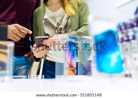 Woman holding mobile phone and black man is pointing finger at phone. They are looking for new smart phone. Mobile shop. Shallow depth of field. - stock photo