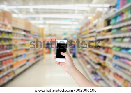 Woman holding mobile phone while shopping in supermarket - stock photo
