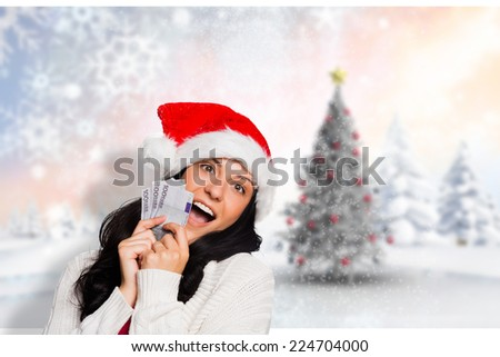 Woman holding money towards herself against blurry christmas scene - stock photo