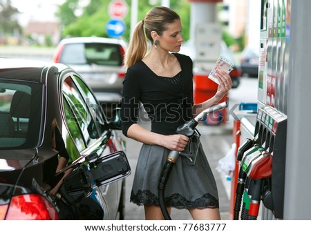 woman holding money when refuel car in gas station - stock photo