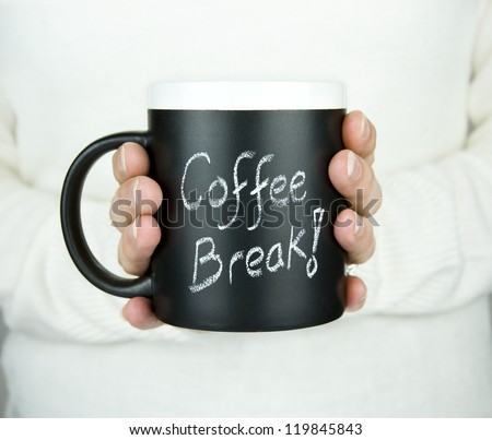 woman holding mug of coffee with coffee break text in chalk