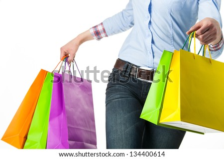 Woman holding multicolored shopping paper bags - closeup shot on white background - stock photo