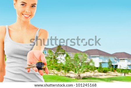Woman holding new keys and looking at camera. Brand new modern houses on background - stock photo
