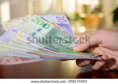 Woman holding new swedish bank notes