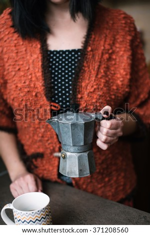 Woman holding old italian coffee maker - stock photo