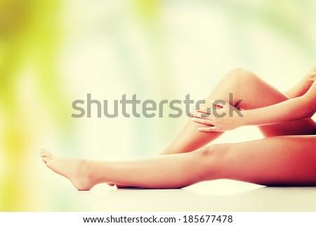 Woman holding on leg. - stock photo