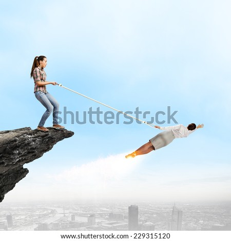 Woman holding on rope businesswoman trying to escape - stock photo
