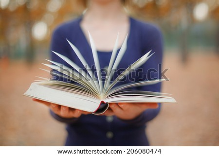 woman holding open book - stock photo