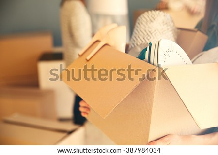 Woman holding open cardboard box with things for moving into new house - stock photo