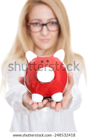 Woman holding out a piggy bank on the white background - stock photo