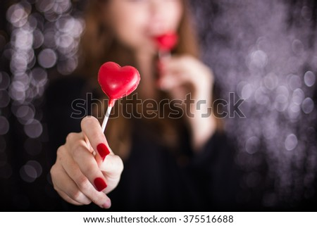Woman Holding out Red Heart Lollipop