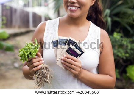 Woman holding packets of organic seeds against a wooden wall. (Written in Spanish: Coriander seeds, mustard seeds, arugula seeds and radish seeds) - stock photo