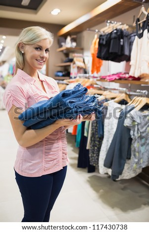 Woman holding pants in her hands standing in a shopping mall - stock photo