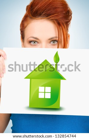 woman holding paper with illustration of green eco house - stock photo