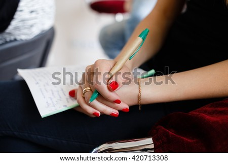 woman holding pen and notebook, hands close-up - stock photo