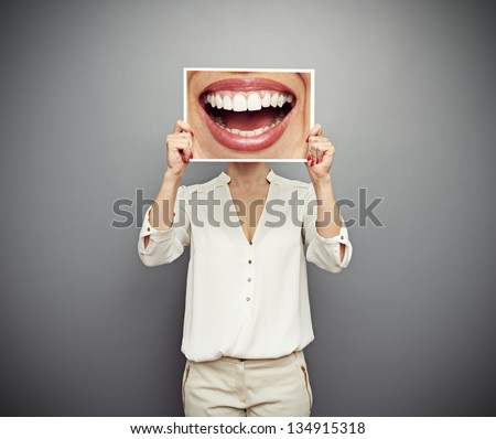 woman holding picture with big smile. concept photo over dark background - stock photo