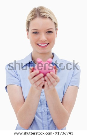 Woman holding piggy bank against a white background - stock photo