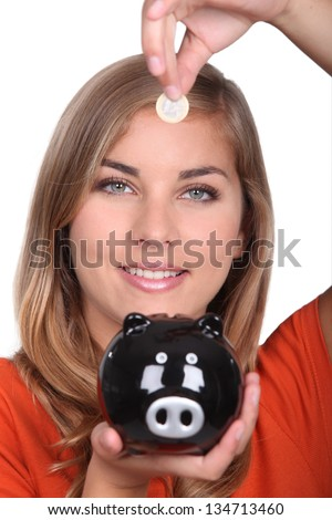 Woman holding piggy bank and coin - stock photo