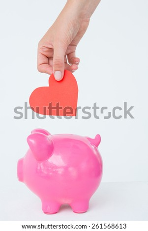 Woman holding piggy bank and red heart on white background