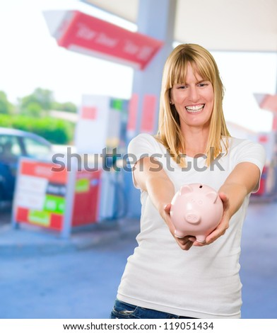 Woman Holding Piggy bank at a petrol station, outdoor - stock photo