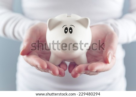 Woman holding piggy coin bank in hands, selective focus with shallow depth of field - stock photo