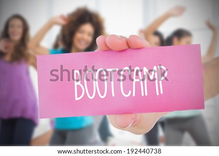 Woman holding pink card saying bootcamp against fitness class in gym - stock photo
