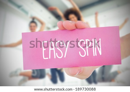 Woman holding pink card saying easy spin against dance class in gym - stock photo