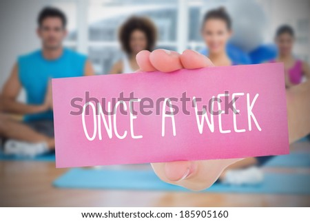 Woman holding pink card saying once a week against yoga class in gym - stock photo