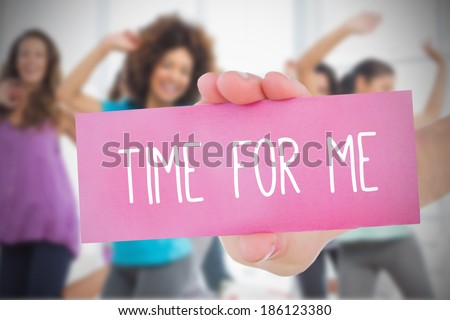Woman holding pink card saying time for me against class in gym - stock photo