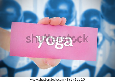 Woman holding pink card saying yoga against fitness class in gym - stock photo