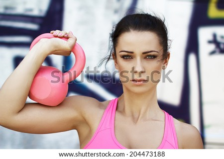 Woman holding pink kettlebell over shoulder, outdoor sport - stock photo