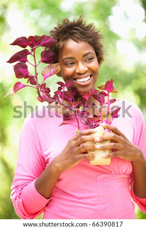 Woman holding plant and smiling - stock photo