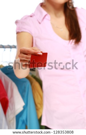 Woman holding plastic card while going shopping - stock photo